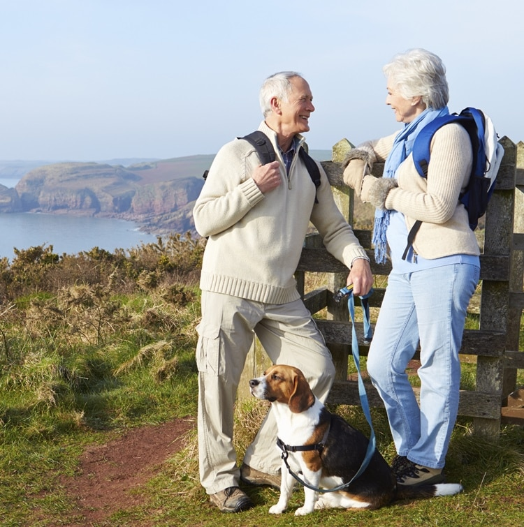 older couple hiking with dog