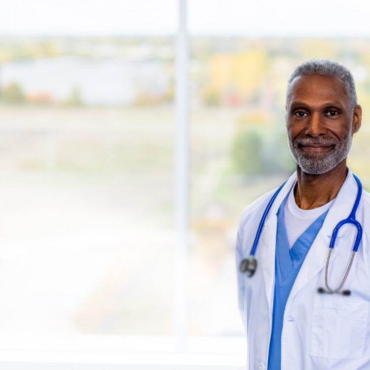 Male doctor smiling and standing a window with a stethoscope around his neck