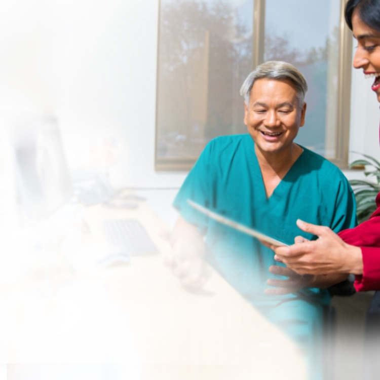 Two healthcare professionals smiling and looking at a tablet