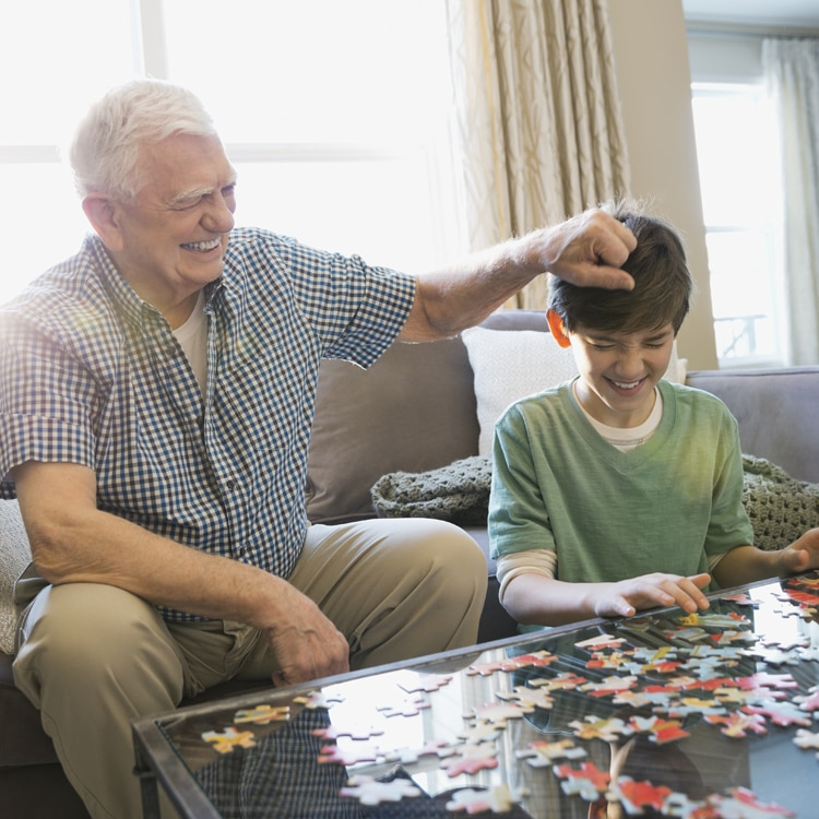Elderly man putting a puzzle together with his grandson.