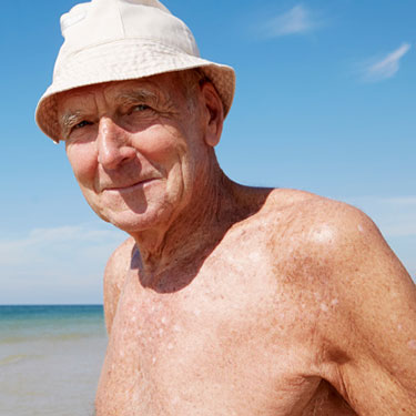 Smiling older gentleman on a beach wearing a hat.