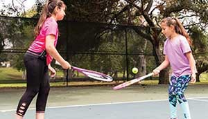 Two young girls play tennis outside.