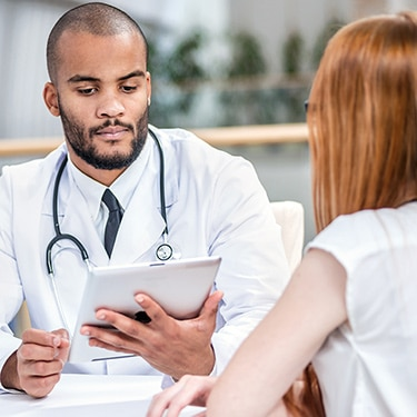 Doctor holding tablet device, consulting patient