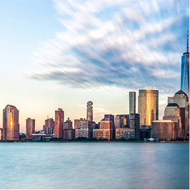 Stylized New York City skyline during the late afternoon, with sunset reflecting off buildings and buildings reflected in the water.