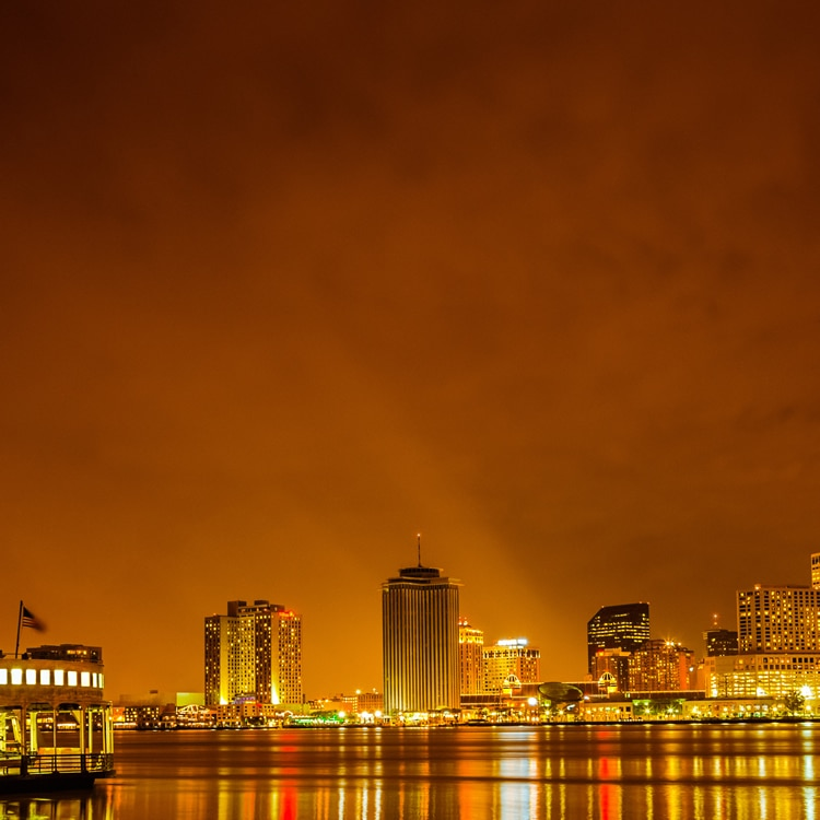 View of New Orleans skyline at night, seen from across the river. The buildings and city lights reflect on the water. A ferry boat is on the river to the left.