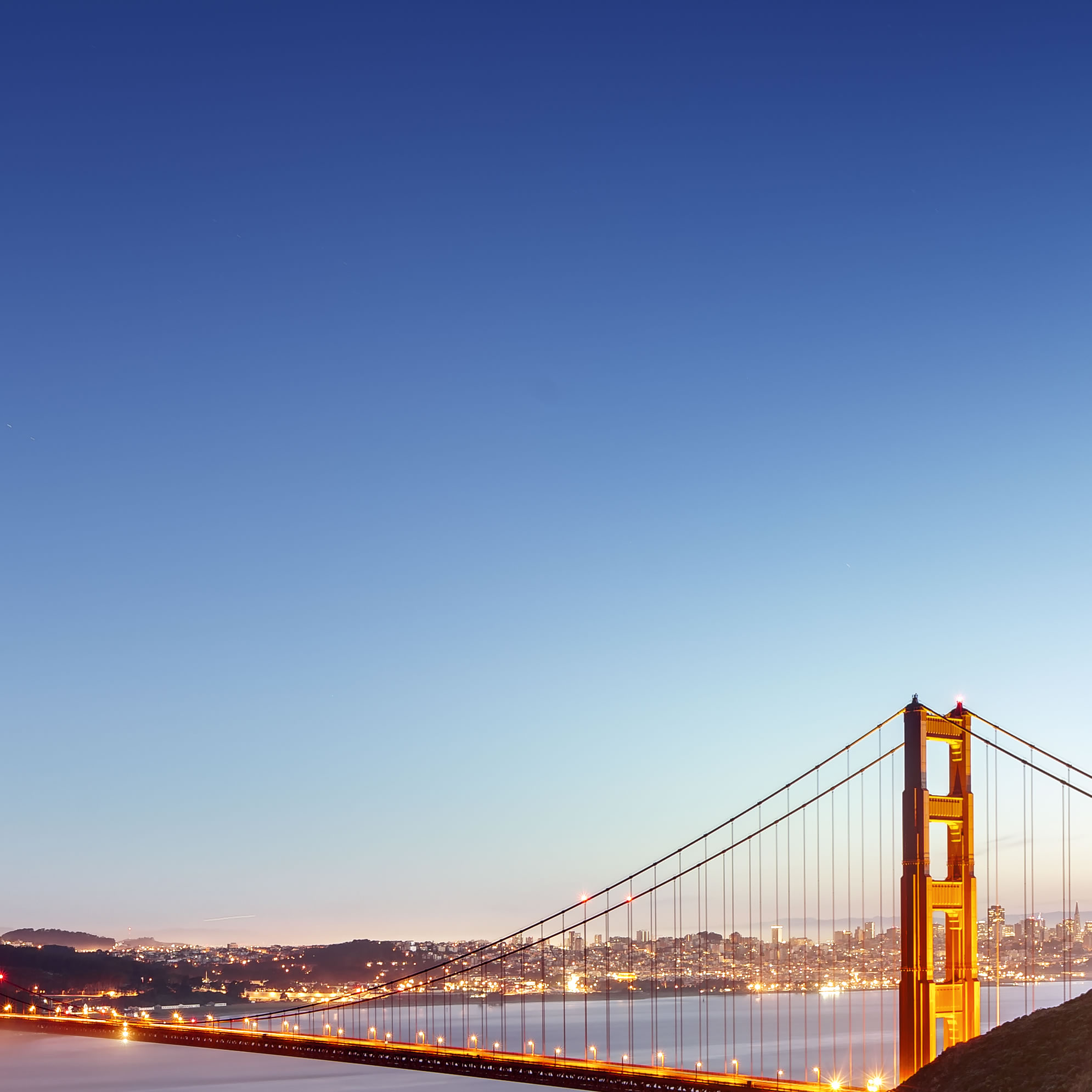 View of Golden Gate Bridge in the evening with San Francisco in the background. City lights visible in the evening light.