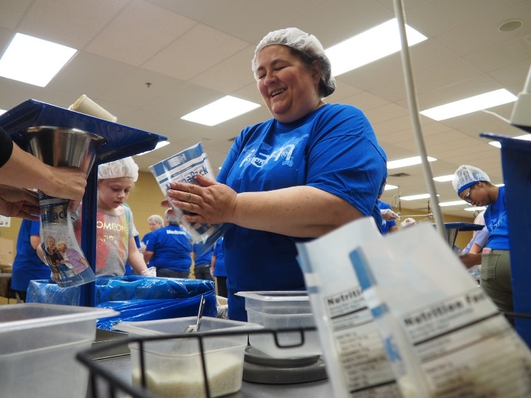 Employees pack food at Feed My Starving Children