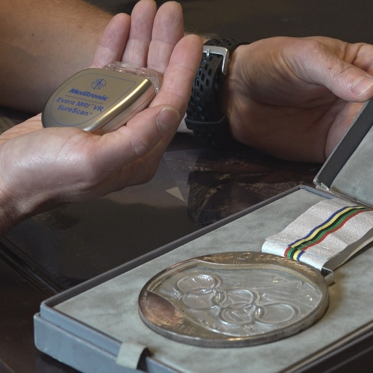 Paul Wylie holds an MRI compatible ICD next to his Olympic Silver Medal
