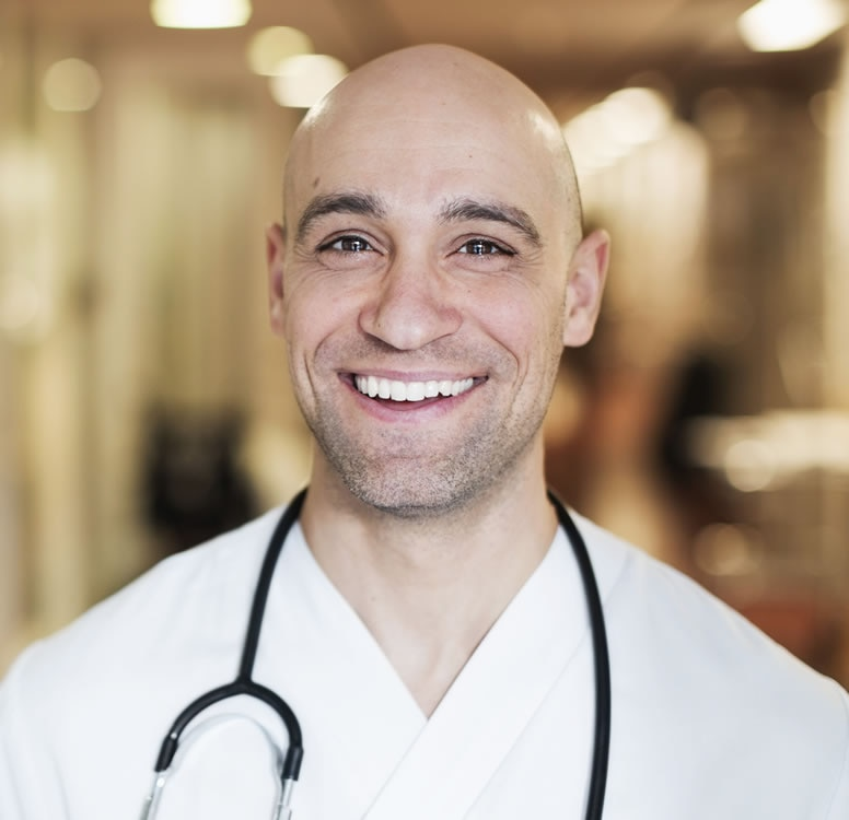 Smiling male physician with a stethoscope in a hospital hallway