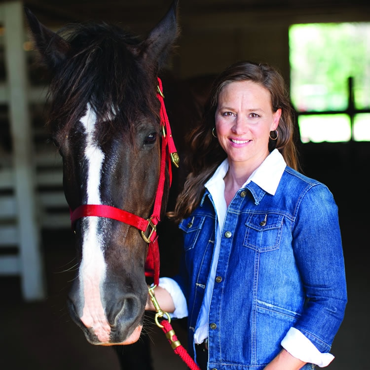 Woman in a stable wearing a denim jacket, with a horse