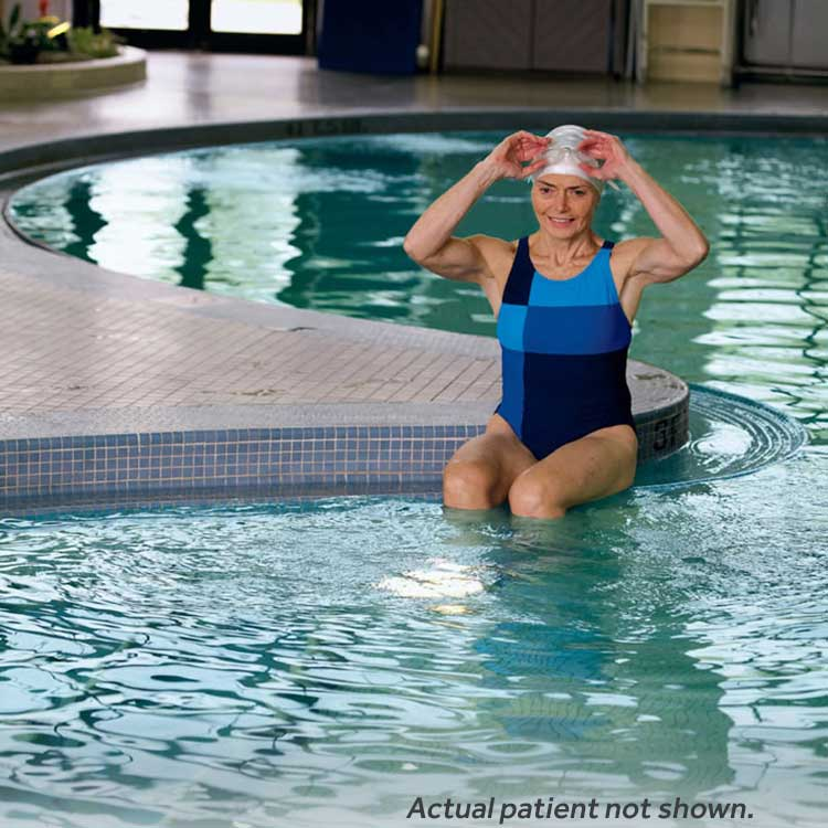 Woman in a swimcap and swim suit getting into a pool