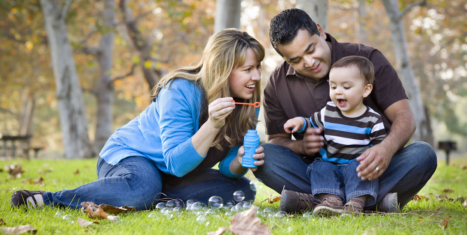 Mother and father playing in a park blowing bubbles with their child