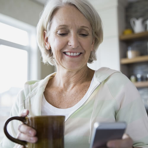 Woman drinking from a tea cup and looking at her phone