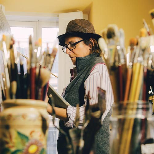 Older woman is painting a canvas with a jar of paintbrushes in the foreground.