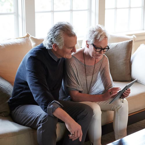 Older couple uses a tablet while sitting on a couch together.